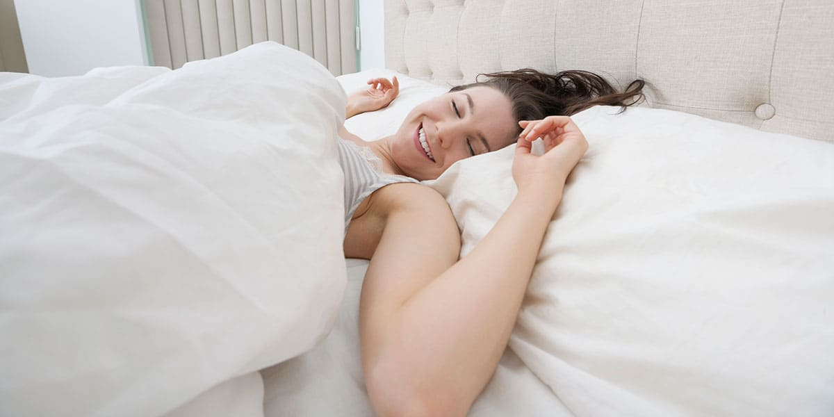 woman lying on bed without night sweats or hot flashes